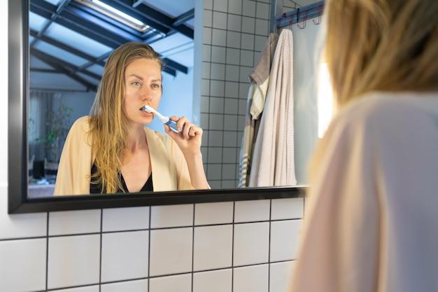 Красивая молодая женщина смотрит в зеркало в ванной, чистит зубы зубной щеткой