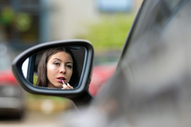 Beautiful young woman looking at rear car mirror applying lipstick
