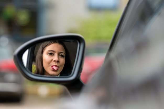 Beautiful young woman looks in the rearview mirror of the car and shows her tongue