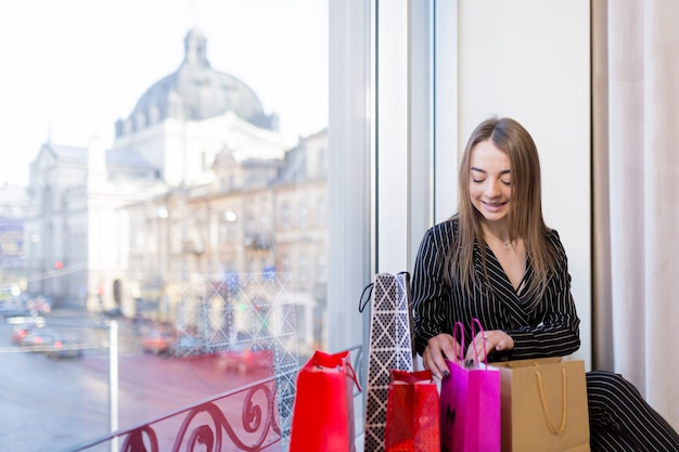 Beautiful young woman looks shopping in paper bags on the hotel window against the old city