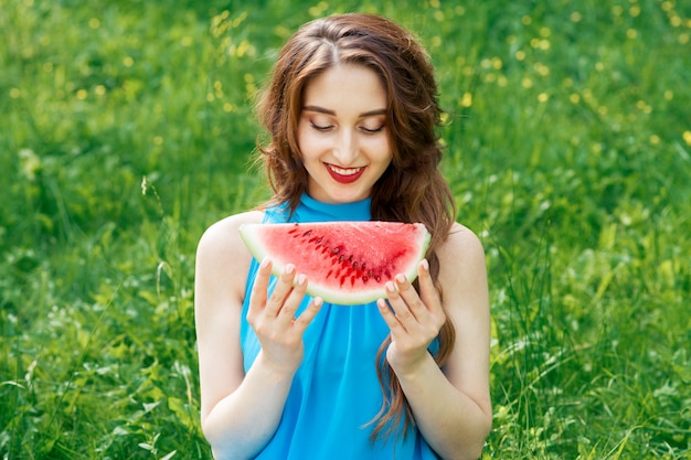 Beautiful young woman looks at the watermelon to eat in summer sunny day.