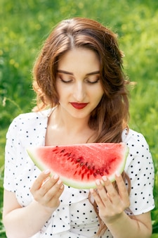 Beautiful young woman looks at watermelon for eating in summer season.