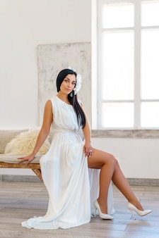 Beautiful young woman in luxury white dress . shooting in a white studio.