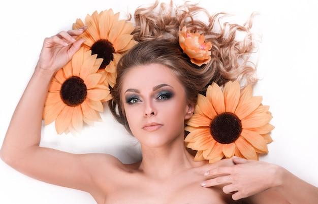 ひまわりの花の間に横たわる美しい若い女性