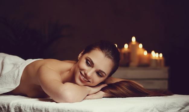 거짓말을 하 고 그녀의 마사지를 기다리고 아름 다운 젊은 여자. 스파 컨셉