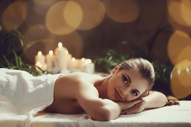 Красивая молодая женщина лежа и ждет ее массажа. концепция спа