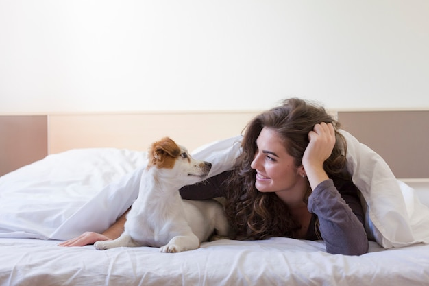 Beautiful young woman lying on bed under the white cover with her cute small dog. home, indoors and lifestyle