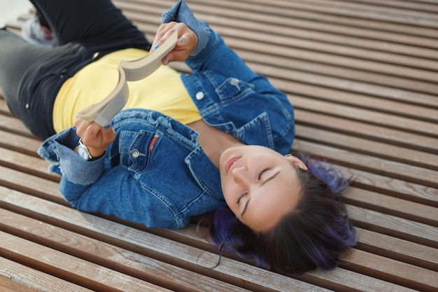 Beautiful young woman lying on a bench, smiling and reading a book