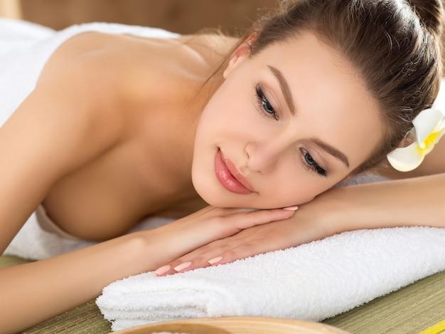 Красивая молодая женщина, лежа в салоне спа. уход за кожей и телом, здоровый образ жизни, отдых