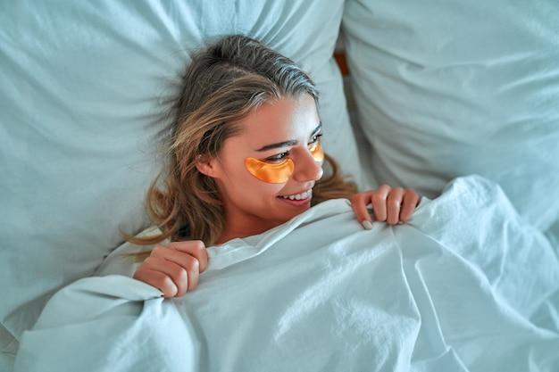 Красивая молодая женщина, лежа в постели и спать. девушка с открытыми глазами закрывает лицо белым одеялом утром. не высыпается концепция. концепция ухода за кожей.