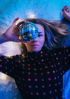 Beautiful young woman lying down with disco ball. party concept. new year christmas or birthday party. joyfull happines and magic dreaming. having fun