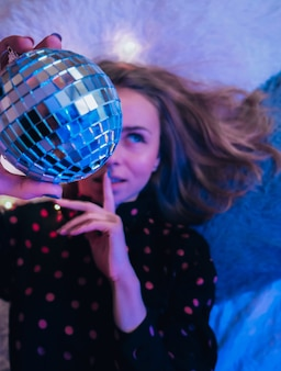 Beautiful young woman lying down with disco ball. party concept. new year christmas or birthday party. joyfull happines and magic dreaming