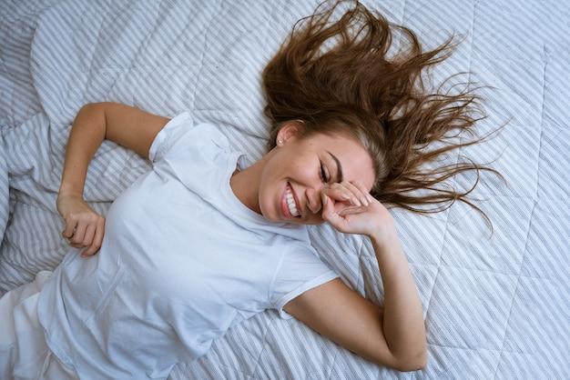 Красивая молодая женщина, лежа в постели, улыбается девушка с открытыми глазами закрывает лицо руками и ...