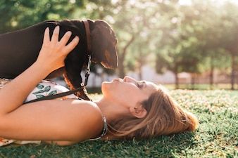 Beautiful young woman lying on green grass kissing her dog at park