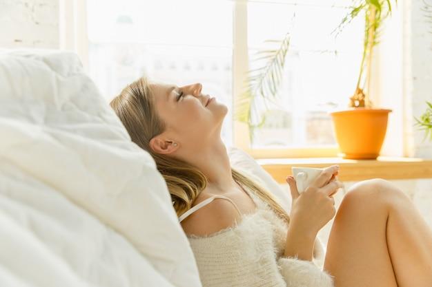 暖かい日光とソファに横たわって美しい若い女性。