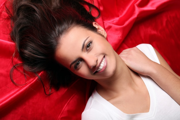 Beautiful young woman lying in red silk, top view