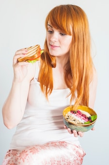 Beautiful young woman making choice between sandwich and oatmeal granola