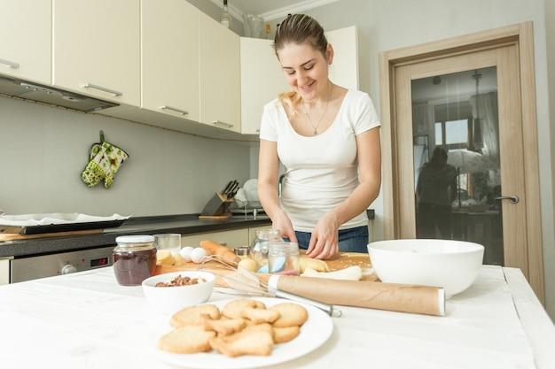 自宅のキッチンで生地を作る美しい若い女性