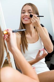 Bella giovane donna che fa trucco vicino allo specchio a casa.