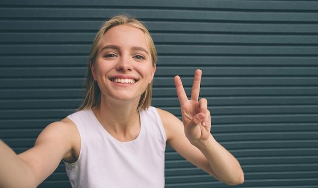 Красивая молодая женщина делает автопортрет на смартфоне на фоне стены