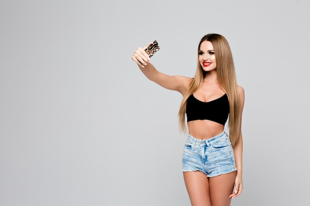 Beautiful young woman making selfie taking pictures of herself on the phone slender girl in a denim outfit with red lips makes a photo of herself on a smartphone