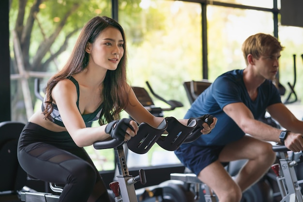 Beautiful young woman and man exercising on stationary bike at fitness gym sport club