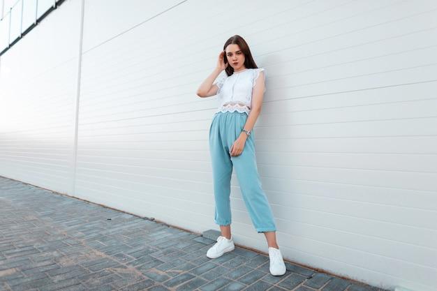 흰색 운동화에 파란색 바지에 세련된 레이스 탑에 아름 다운 젊은 여자 모델은 도시의 현대적인 건물 근처에 서 있습니다. 예쁜 여자 야외. 여성 의류의 유행 여름 컬렉션.