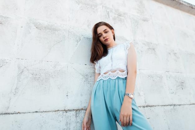 흰 벽 근처 도시에서 포즈를 취하는 트렌디 한 블루스 바지에 세련된 레이스 흰색 블라우스에 아름 다운 젊은 여자 모델. 야외 도시 우아한 갈색 머리 소녀. 유행 여성 여름 옷.