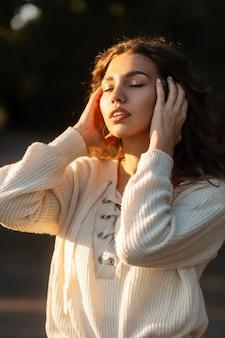 곱슬 머리와 니트 스웨터에 귀여운 얼굴을 가진 아름 다운 젊은 여성 모델은 일몰에 자연에서 휴식을 취합니다. 조용하고 평화로운 예쁜 소녀 야외