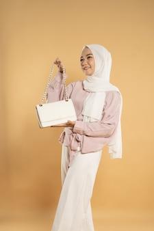 Красивая молодая женщина-мусульманка азиатского происхождения, на светлом изолированном фоне, одетая в современный стиль хиджаба