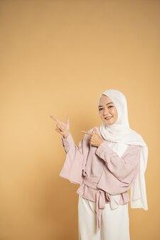 Представляя мусульманскую азиатскую женщину красивой молодой женщины, одетую в современном стиле хиджаба