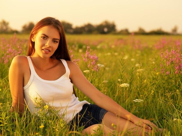 Bella giovane donna sulla natura su sfondo campo estivo.
