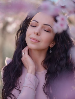A beautiful young woman near a blooming spring cherry blossom tree. a celebration of spring and blossom like in japan