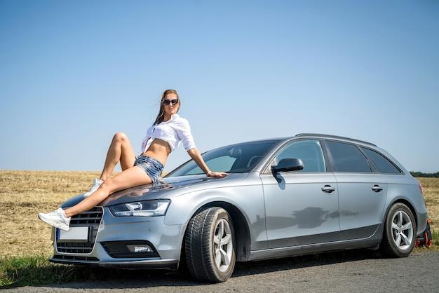 Красивая молодая женщина возле автомобиля, припаркованного на обочине дороги. удовольствие от путешествия.