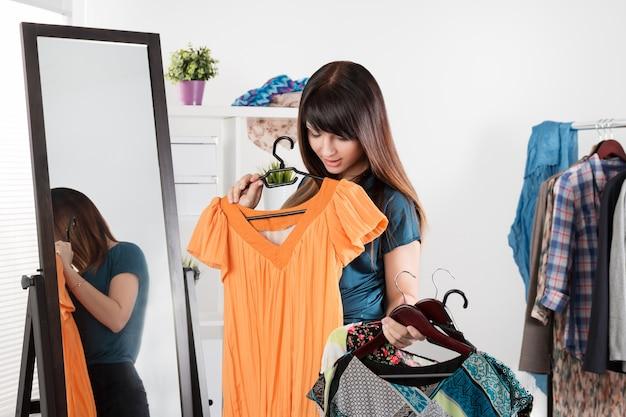 Chioce를 만드는 옷 선반 근처 아름 다운 젊은 여자