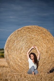 Beautiful young woman near a sheaf of hay in a field. holidays in the village, a girl enjoying nature in a mown field on a sunny day
