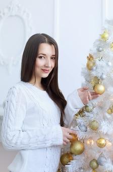 크리스마스 트리 근처 아름 다운 젊은 여자