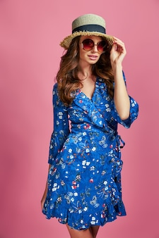 Beautiful young woman in nice blue flower print spring dress and straw hat in a studio fashion spring summer photo emotions pink background