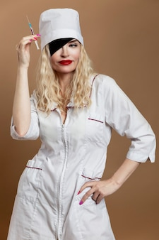 Beautiful young woman in nurse uniform with a syringe in her hand and a black eye patch. sexy blonde with red lips. compulsory vaccination. vertical.