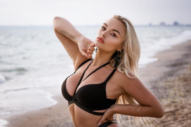 海岸でポーズをとって黒い水着で長いブロンドの髪を持つ外観の美しい若い女性