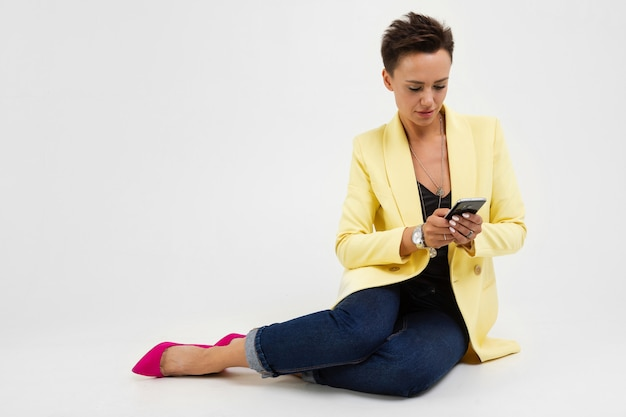Beautiful young woman in office suit sits on the white floor and serfing internet with her phone