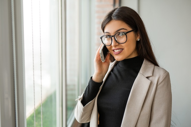 Beautiful young woman in office with cellphone wearing glasses