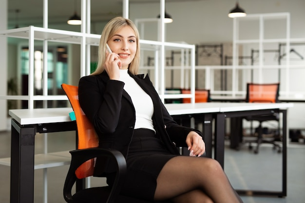 Beautiful young woman in the office with a mobile phone