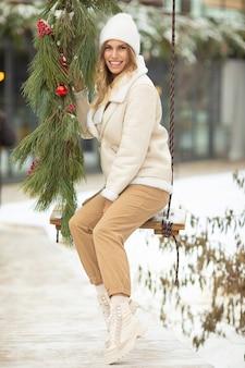 雪の降る冬の散歩にブランコで美しい若い女性。冬の休暇のためのアウトドアの楽しみ。