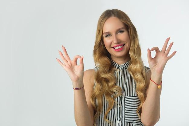 手のジェスチャーで白い壁に美しい若い女性