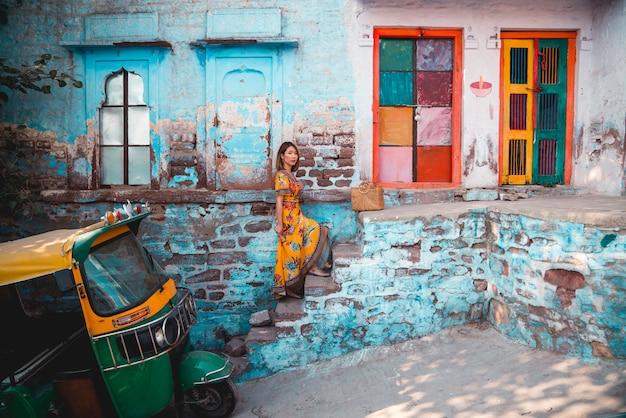 青い街の青/青緑色の背景に美しい若い女性。ジョードプル。インド
