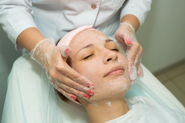 美容でプロシージャを洗浄する顔に美しい若い女性