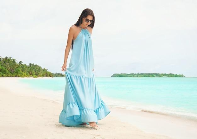 トロピカル リゾートの海のビーチで美しい若い女性