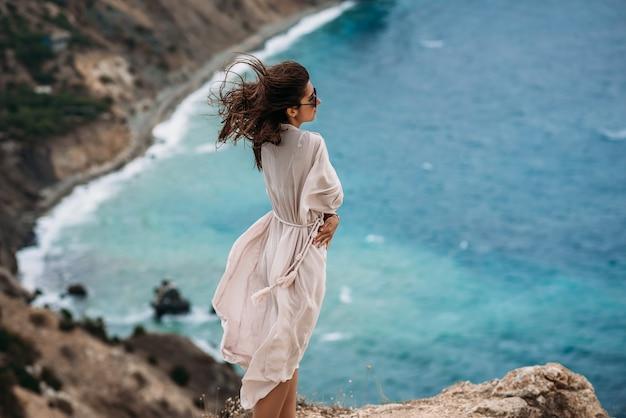 해변에서 아름 다운 젊은 여자. 바다 배경 바위 해변에서 포즈를 취하는 긴 머리를 가진 매력적인 갈색 머리 소녀의 초상화. 바다에서 휴가. 복사 공간