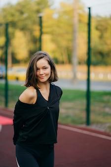 正面を見て遊び場で美しい若い女性